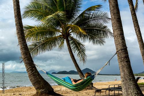 Fototapeten Strand Woman laying in hammock between palm trees
