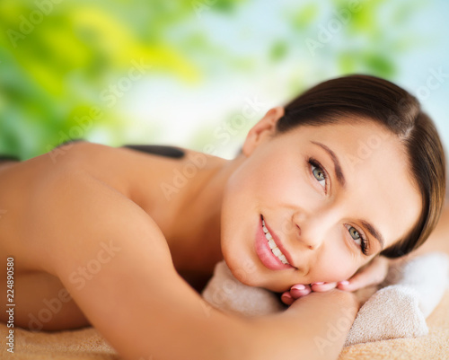 wellness, spa and beauty concept - close up of beautiful woman having hot stone therapy over green natural background © Syda Productions