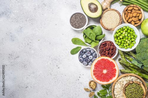 Foto Murales Superfoods on light stone background. Healthy vegan food.