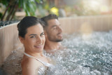 Couple relaxing in spa resort hot pool