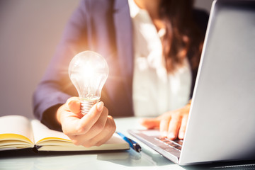 Businesswoman Holding Illuminated Light Bulb