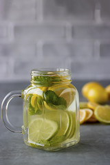 Refreshing lemonade with lemon and lime slices and mint leaves in a glass mug on a gray background.