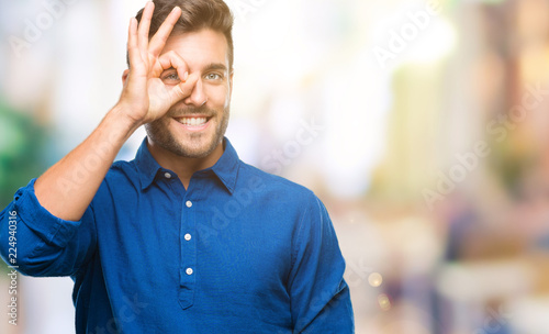 Leinwanddruck Bild Young handsome man over isolated background doing ok gesture with hand smiling, eye looking through fingers with happy face.