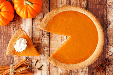 Pumpkin pie with slice removed. Top view table scene on a rustic wood background.