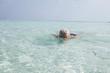 Blonde woman swimming on Maldives