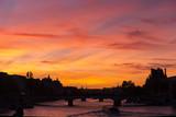 Spectacular crimson sunset over the Seine River in Paris