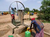 donna africana raccoglie l'acqua al pozzo  - 224983500