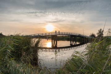 Set walks over bridge at sunset