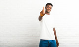 Dark skinned man showing and lifting a finger in sign of the best - 225011721