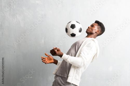 Leinwanddruck Bild African american sportman holding a soccer ball