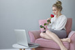 Leinwandbild Motiv Horizontal shot of fashionable young female in white blouse and skirt relaxing in armchair, holding one red rose, inhaling sweet aroma, deep in thoughts, open laptop resting on round table