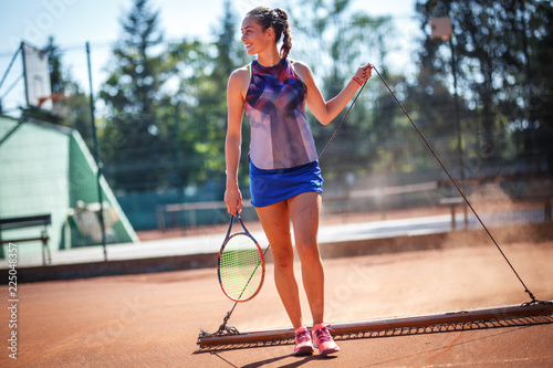 Fototapeta Female tennis player cleaning the court with drag mat.