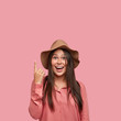 Indoor shot of pleasant looking satisfied girlfriend points with index finger upwards, shows free space for your advertisement, smiles positively, wears fashionable clothes, isolated on pink wall