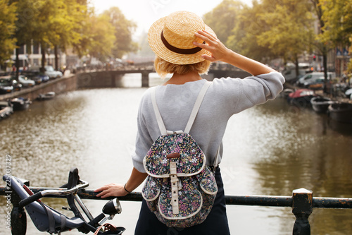Happy traveler girl enjoying Amsterdam city. Tourist woman looking to the Amsterdam canal, Netherlands, Europe