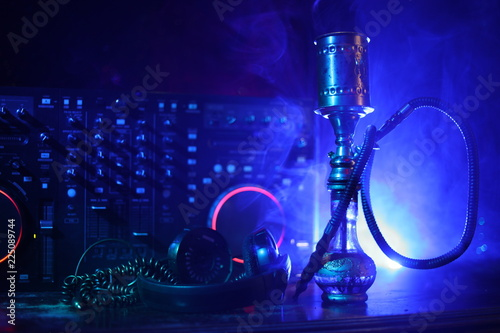 Leinwanddruck Bild Shisha party club concept. Dj mixer with on dark nightclub background with stylish oriental shisha.