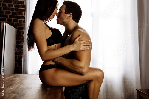 Leinwanddruck Bild Couple. Sex. Passion. Young sexy man and woman are kissing before having sex on the table