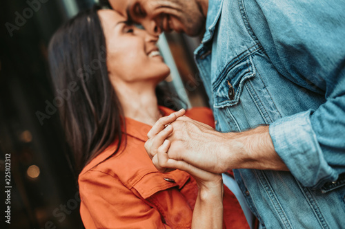 Leinwanddruck Bild I love you. Positive male touching hand of cheerful lady while telling with her outdoor