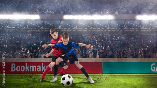 two kids fotball players struggling for the ball