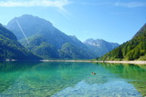 Lago del Predil (Predil Lake), small mountain lake with turquoise water in Julian Alps, Tarvisio with mountains in background, Italy