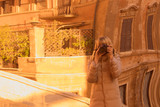 A young tourist woman are photographed in reflection in a mirror in the streets of Rome Italy. Blured image, reflection.