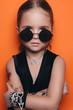 Fashion young model on an orange background, fashion kis in a black sunglasses, fashion portrait