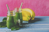 Green smoothies in glass bottles on cool pink blue background with yellow bananas, selective focus