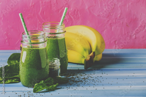 Leinwandbild Motiv Green smoothies in glass bottles on cool pink blue background with yellow bananas, selective focus