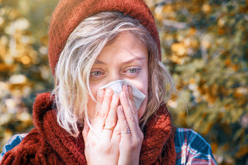 Woman portrait outdoor sneezing because cold and flu