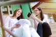 Two cheerful young school girls sitting on school staircases and putting makeup on. One is learning while other is putting her makeup on.