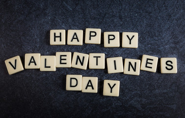 Scrabble letter tiles on black slate background spelling happy valentines day