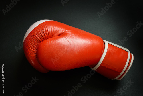 Old and used boxing glove on dark background.
