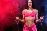 Muscular young fit sports woman athlete. Workout with bands or expander in gym on black background. Copy space for fitness nutrition ads.
