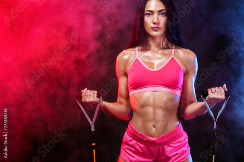 Muscular young fit sports woman athlete. Workout with bands or expander in gym on black background. Copy space for fitness nutrition ads. © Mike Orlov