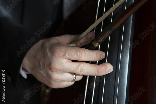 Hands of a musician playing on a contrabass closeup - 225168192