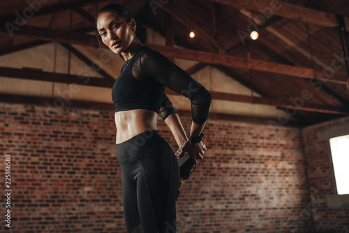 Foto Murales Woman relaxing her leg muscles at gym