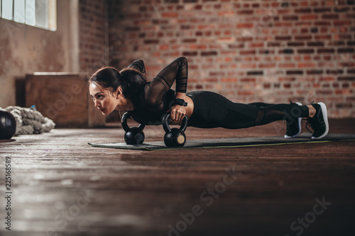 Leinwanddruck Bild Fit female doing intense core workout in gym