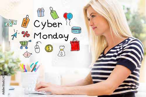 Cyber Monday with happy young woman sitting at her desk in front of the computer