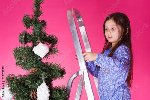 Leinwandbild Motiv Little girl with christmas tree on pink background