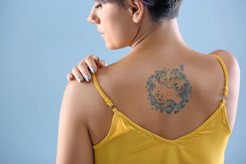 Young woman with tattoo on color background