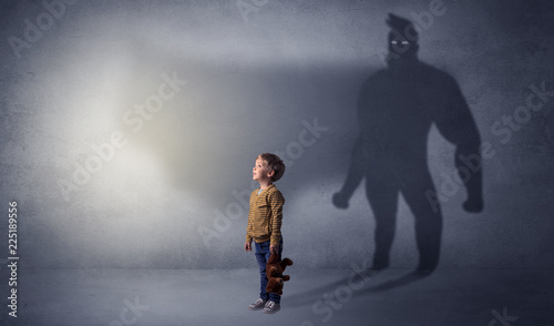 Leinwanddruck Bild Cute kid in a room with plush on his hand and hero shadow on his background