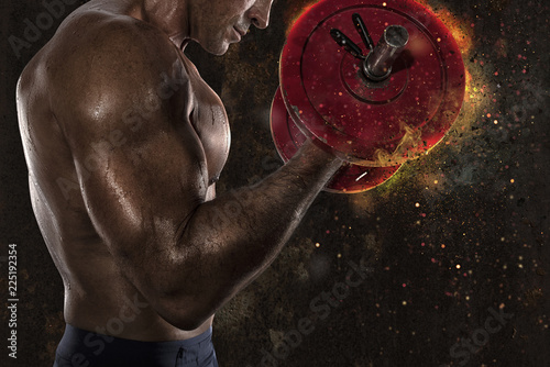 Athletic man training biceps at the gym with fire effect - 225192354