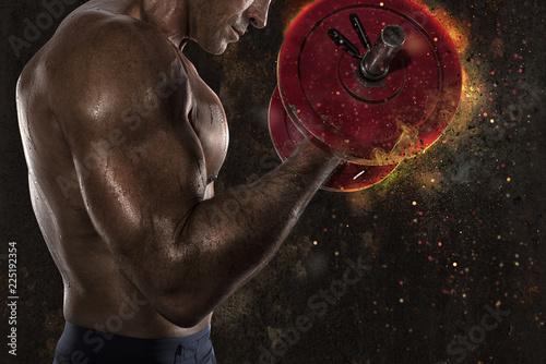 Leinwandbild Motiv Athletic man training biceps at the gym with fire effect