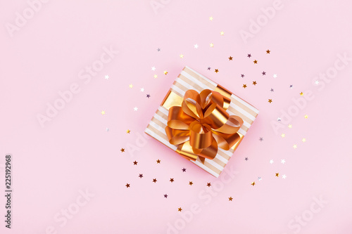 Leinwandbild Motiv Gift or present box and stars confetti on pink table top view. Flat lay composition for birthday, christmas or wedding.