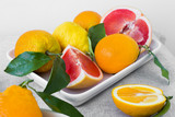 Citrus fruits on plate. Oranges, grapefruits and lemons with leaves.