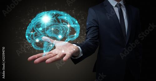 Leinwanddruck Bild Businessman holding human brain on his hand with logistics symbols around