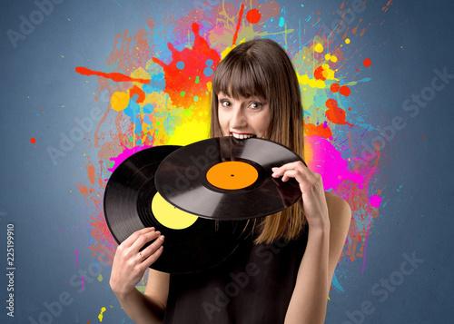 Młoda dama trzyma winylowego rejestr na szarym tle z kolorowymi pluśnięciami za ona