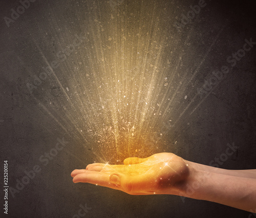 Yellow ray of light coming from a young hand