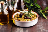 Olives. Bottle virgin olive oil and oil in a bowl with some olives - 225209165