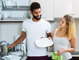 Black man with white woman dusting in domestic kitchen - 225212352