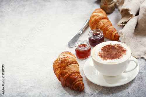 Cup of cappuccino coffee with croissants
